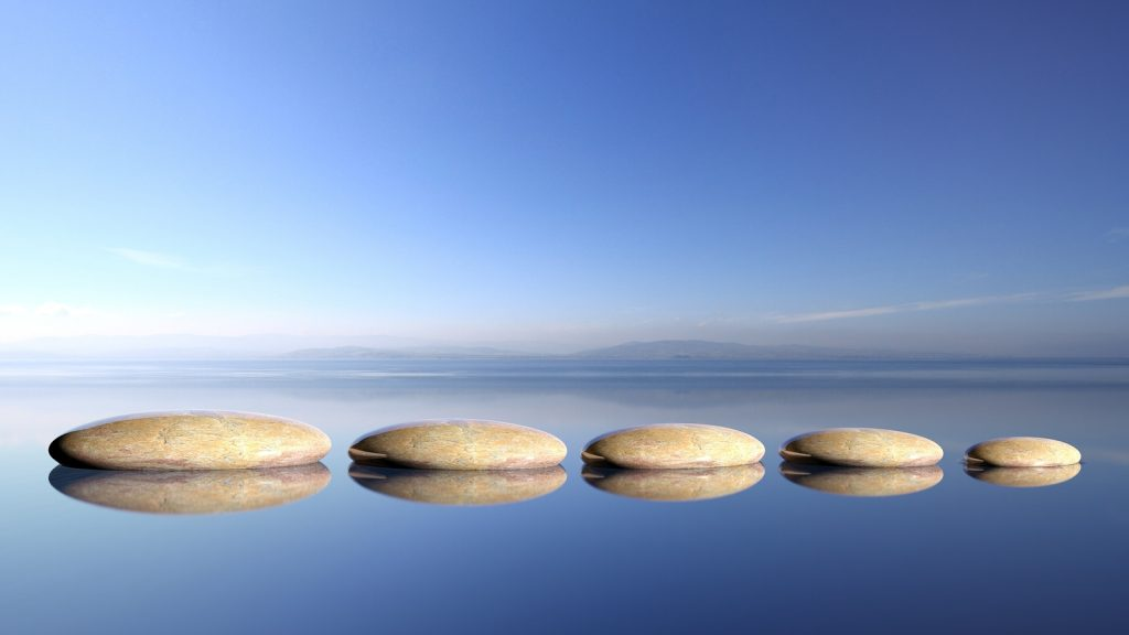 Zen stones row from large to small  in water with blue sky and p